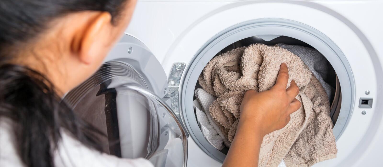 Kvinde tager tøj ud af vaskemaskine