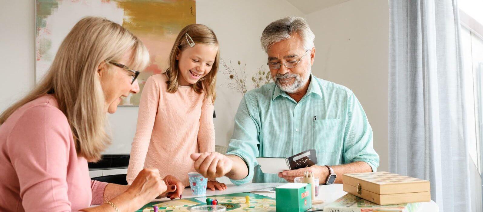 Familie spiller spil ved bord